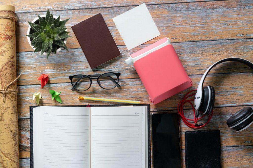 Glasses, passport, notepad and headphones