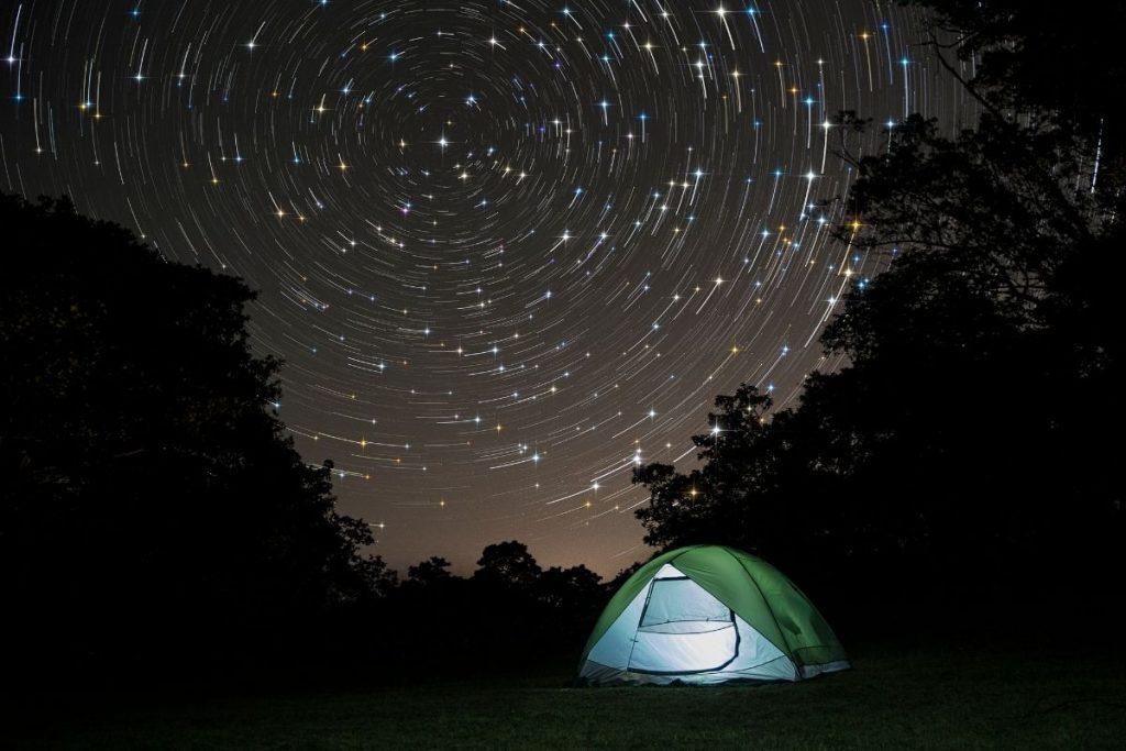 Tent under a black star sky