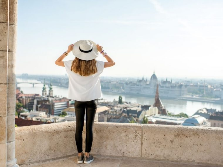Woman wearing a hat looking over a city